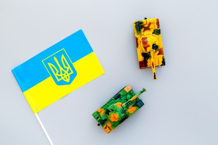 War, military threat, military power concept. Ukraine. Tanks toy near Ukrainian flag on grey background top view Stock Photo - 116357114