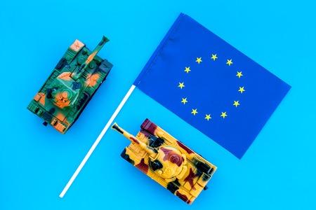 War, military threat, military power concept. European Union. Tanks toy near European flag on blue background top view