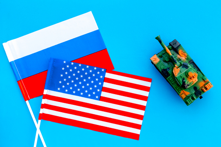 War, confrontation concept. Russia, USA. Tanks toy near Russian and American flag on blue background top view