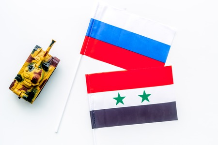 War, confrontation concept. Russia, Syria. Tanks toy near Russian and Syrian flag on white background top view. Imagens