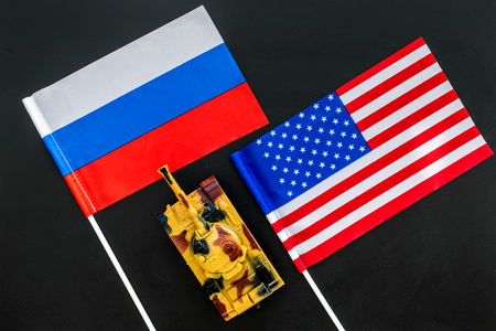 War, confrontation concept. Russia, USA. Tanks toy near Russian and American flag on black background top view.