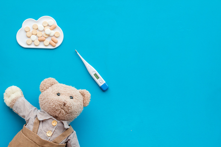 Childhood diseases concept. Treatment of children. Teddy bear toy, thermometer and pills on blue background top view space for text