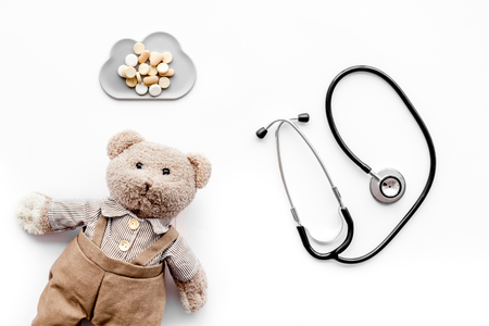 Children's doctor concept. Teddy bear toy, pills and stethoscope on white background top view