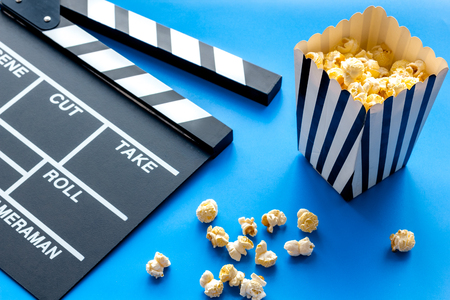 Film watching concept. Clapperboard and popcorn on blue background Banque d'images - 116443310