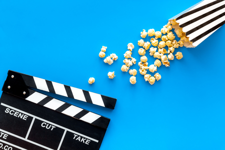 Film watching concept. Clapperboard and popcorn on blue background top view copy space Banque d'images - 116443311