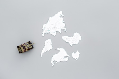 Military action, military threat concept. Tanks toy on world map on grey background top view copy space Stock Photo