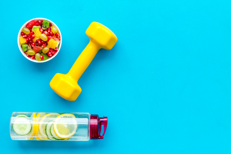 Healthy lifestyle, healthy habits. Detox water, fruit salad, sport equipment dumbbells on blue background top view space for text 写真素材