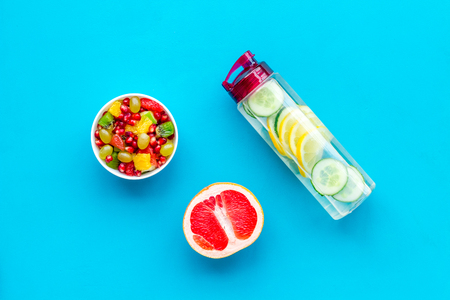 Diet rich in fruits. Slimming diet. Fruit salad near fruit lemon and cucumber water on blue background top view