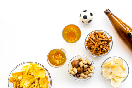 Snacks for watching football on TV. Watching sports. Chips, nuts, rusks near beer and soccer ball on white background top view copy space