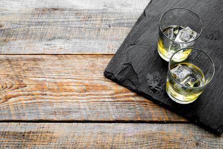 In the bar. Whiskey with ice on black desk on wooden background top view copy space