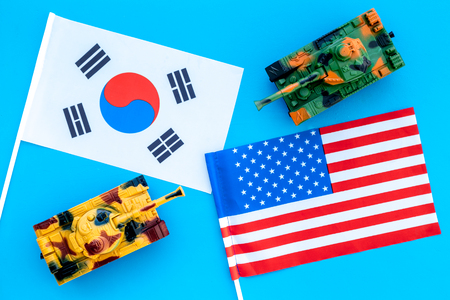 War, confrontation concept. Korea, USA. Tanks toy near Korean and American flag on blue background top view