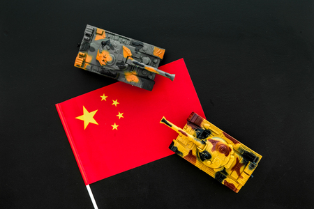 War, military threat, military power concept. China. Tanks toy near Chinese flag on black background top view