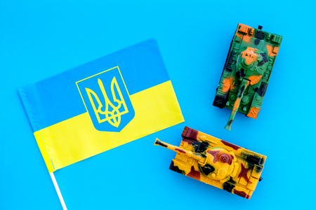 War, military threat, military power concept. Ukraine. Tanks toy near Ukrainian flag on blue background top view