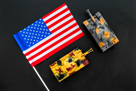 War, military threat, military power concept. USA. Tanks toy near American flag on black background top view Stock fotó