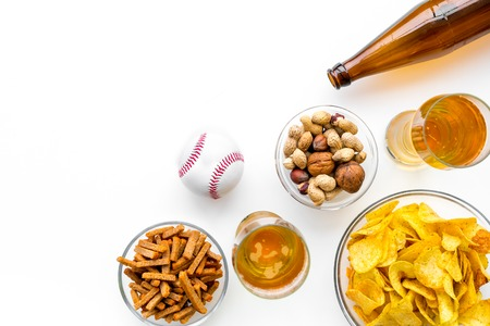 Snacks for watching American football on TV. Watching sports. Chips, nuts, rusks near beer and ball on white background top view copy space Stock Photo