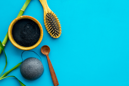 Hair care, hair spa. Cosmetics based on bamboo charcoal powder near comb on blue background top view space for text Stock Photo - 116569109