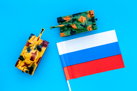 War, military threat, military power concept. Russia. Tanks toy near Russian flag on blue background top view Stock Photo