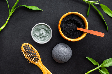 Hair care, hair spa. Cosmetics based on bamboo charcoal powder near comb on black background top view