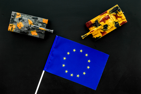 War, military threat, military power concept. European Union. Tanks toy near European flag on black background top view.