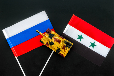 War, confrontation concept. Russia, Syria. Tanks toy near Russian and Syrian flag on black background top view.