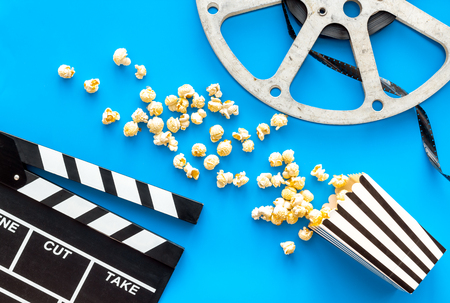 Cinema concept. Clapperboard, film stock, popcorn on blue background top view. Banque d'images - 116569177