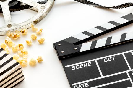 Cinema concept. Clapperboard, film stock and popcorn on white background. Banque d'images - 116569179