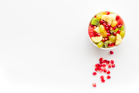 Fruit diet concept. Fruit salad with apple, kiwi and pomegranate in bowl on white background top view.