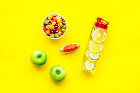 Weight loss concept. Fruit salad near fruit lemon and cucumber water on yellow background top view. Stock Photo