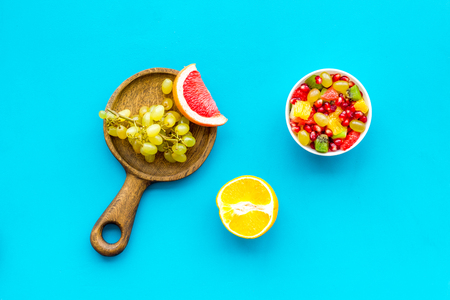 Food rich by vitamins and fiber. Healthy food. Fruit salad near fresh fruits on blue background top view.