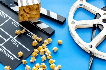 Cinema concept. Clapperboard, film stock and popcorn on blue background. Stock Photo