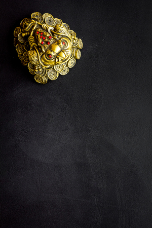 Buddhist symbol. Oriental three legged toad with gold coins on black background top view. Stock Photo - 116569189