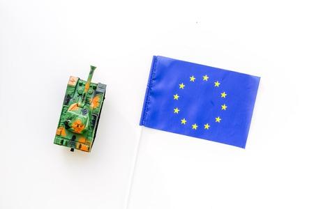 War, military threat, military power concept. European Union. Tanks toy near European flag on white background top view.