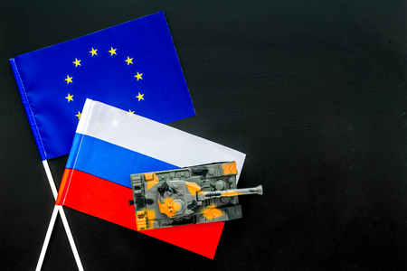 War, confrontation concept. European Union, Russia. Tanks toy near European and Russian flag on black background top view. Stock Photo