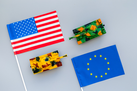 War, confrontation concept. European Union, USA. Tanks toy near European and American flag on grey background top view.