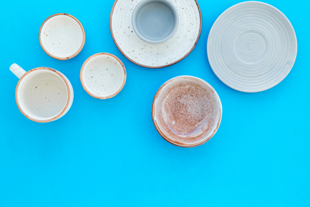 Kitchen concept. Crockery kit. Empty ceramic plates and mugs on blue background top view copy space