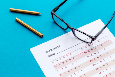 Take the exam. Exam sheet near glasses and pencil on blue background Stock Photo - 116650856