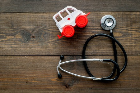 Ambulance service concept. Ambulance vehicle toy near stethoscope on dark wooden background top view space for text Foto de archivo