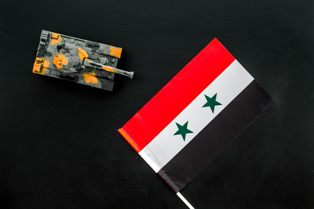 War, military threat, military power concept. Syria. Tanks toy near Syrian flag on black background top view
