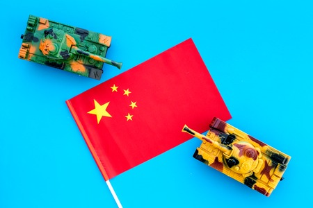 War, military threat, military power concept. China. Tanks toy near Chinese flag on blue background top view