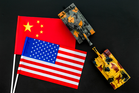 War, confrontation concept. China, USA. Tanks toy near Chinese and American flag on black background top view