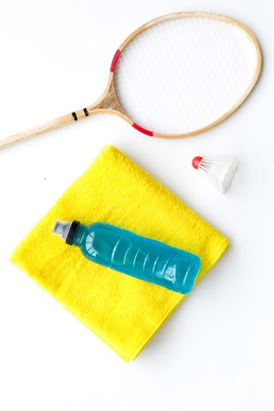 Badminton training concept. Badminton racket, shuttlecock, sport drink and towel on white background top view