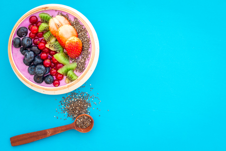 Superfoods. Acai smoothie bowl with fresh fruits, berries, chia seeds on blue background top view space for text