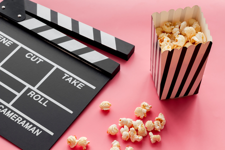 Film watching concept. Clapperboard and popcorn on pink background Banque d'images - 116650944