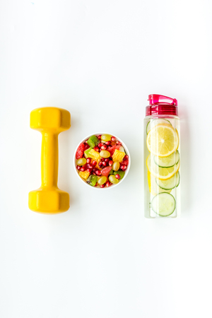 Healthy lifestyle, healthy habits. Detox water, fruit salad, sport equipment dumbbells on white background top view copy space 版權商用圖片
