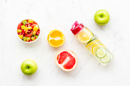 Diet rich in fruits. Slimming diet. Fruit salad near fruit lemon and cucumber water on white background top view