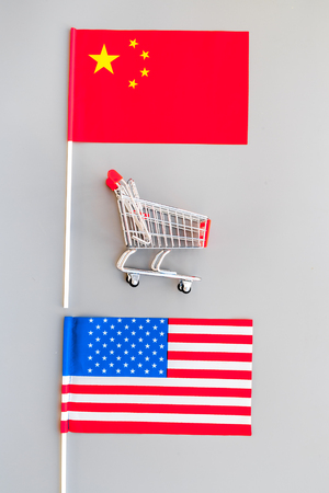 USA and China trade war. American and Chinese flags near shopping chart on grey background top view