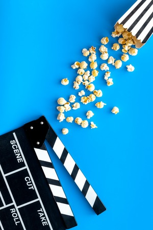 Film watching concept. Clapperboard and popcorn on blue background top view copy space 版權商用圖片