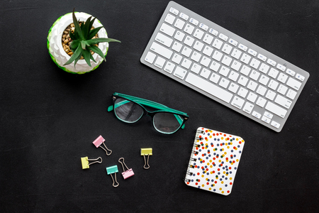 Work desk of manager. Computer keyboard, glasses, stationery, plant on black background top view Stock fotó