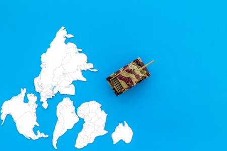Military action, military threat concept. Tanks toy on world map on blue background top view copy space