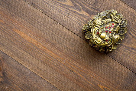 Buddhist symbol. Oriental three legged toad with gold coins on dark wooden background top view copy space